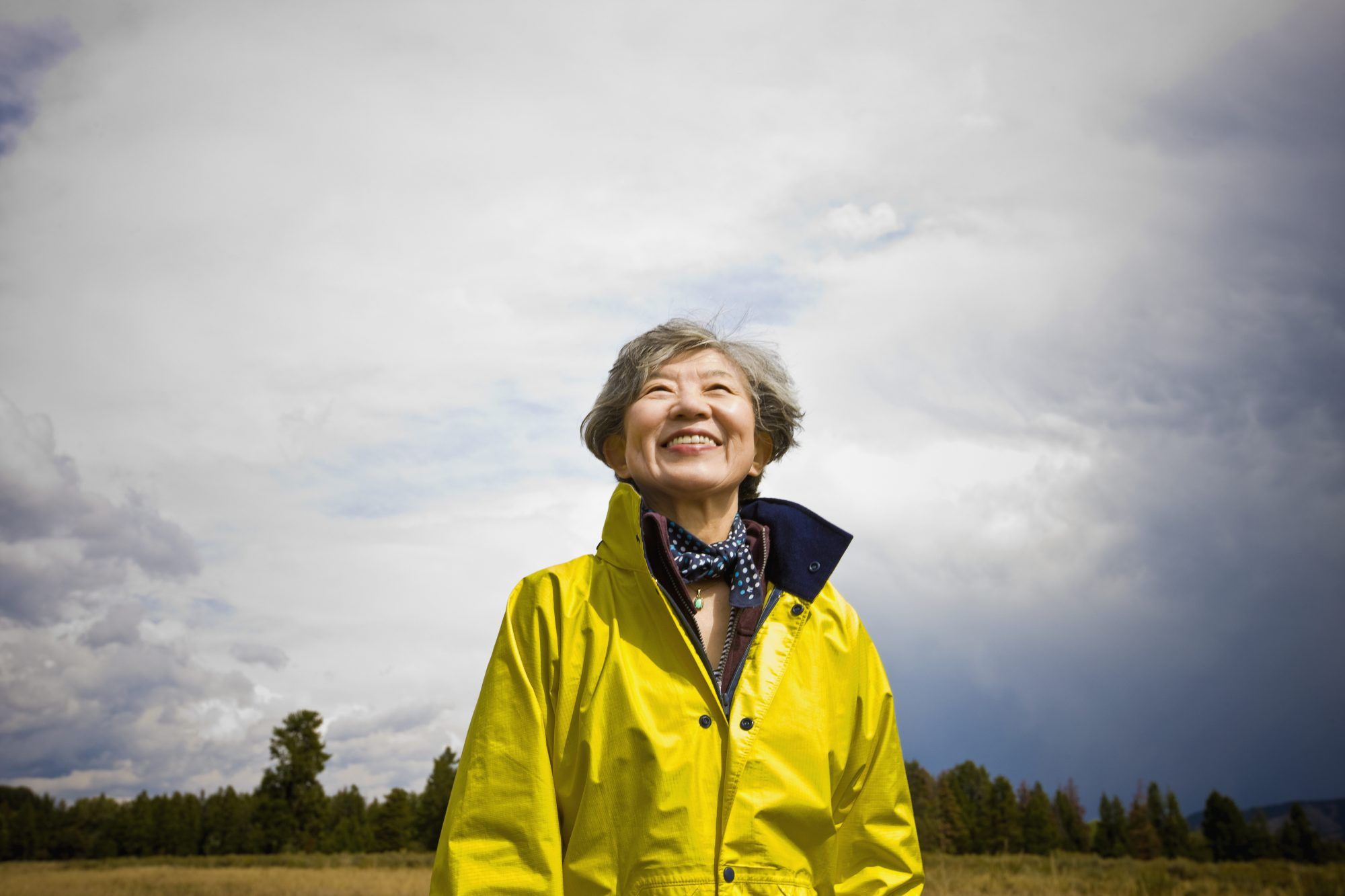 Woman Smiling in Yellow Raincoat