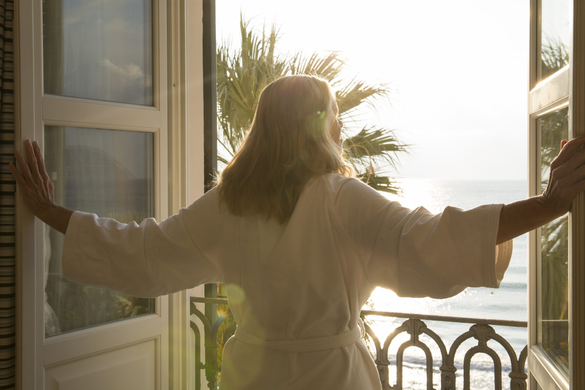 Woman Looking Out Window Hotel Room