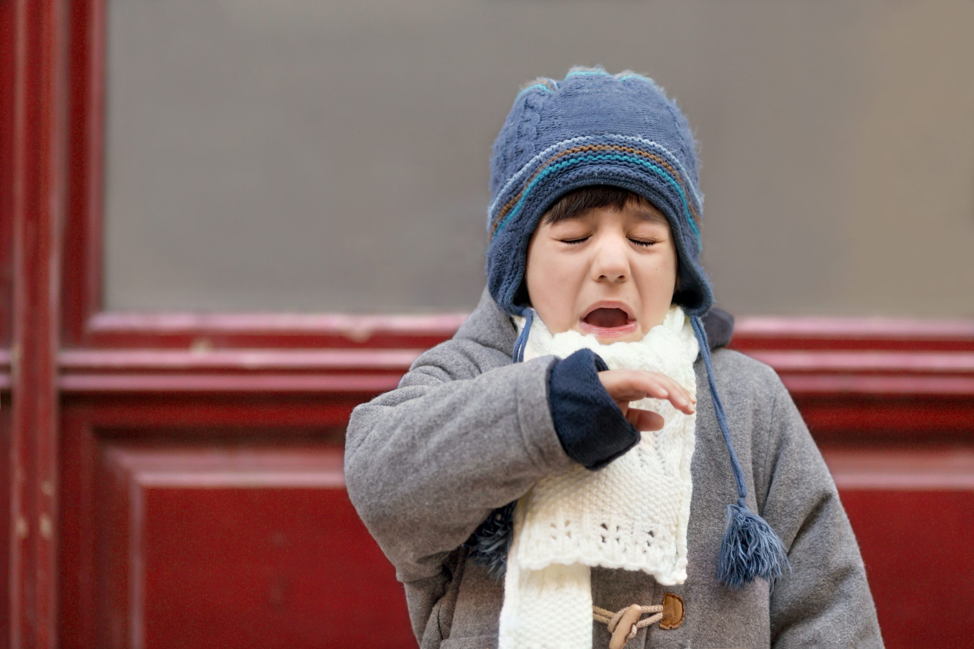 Boy Sneezing Outside in Winter Clothes