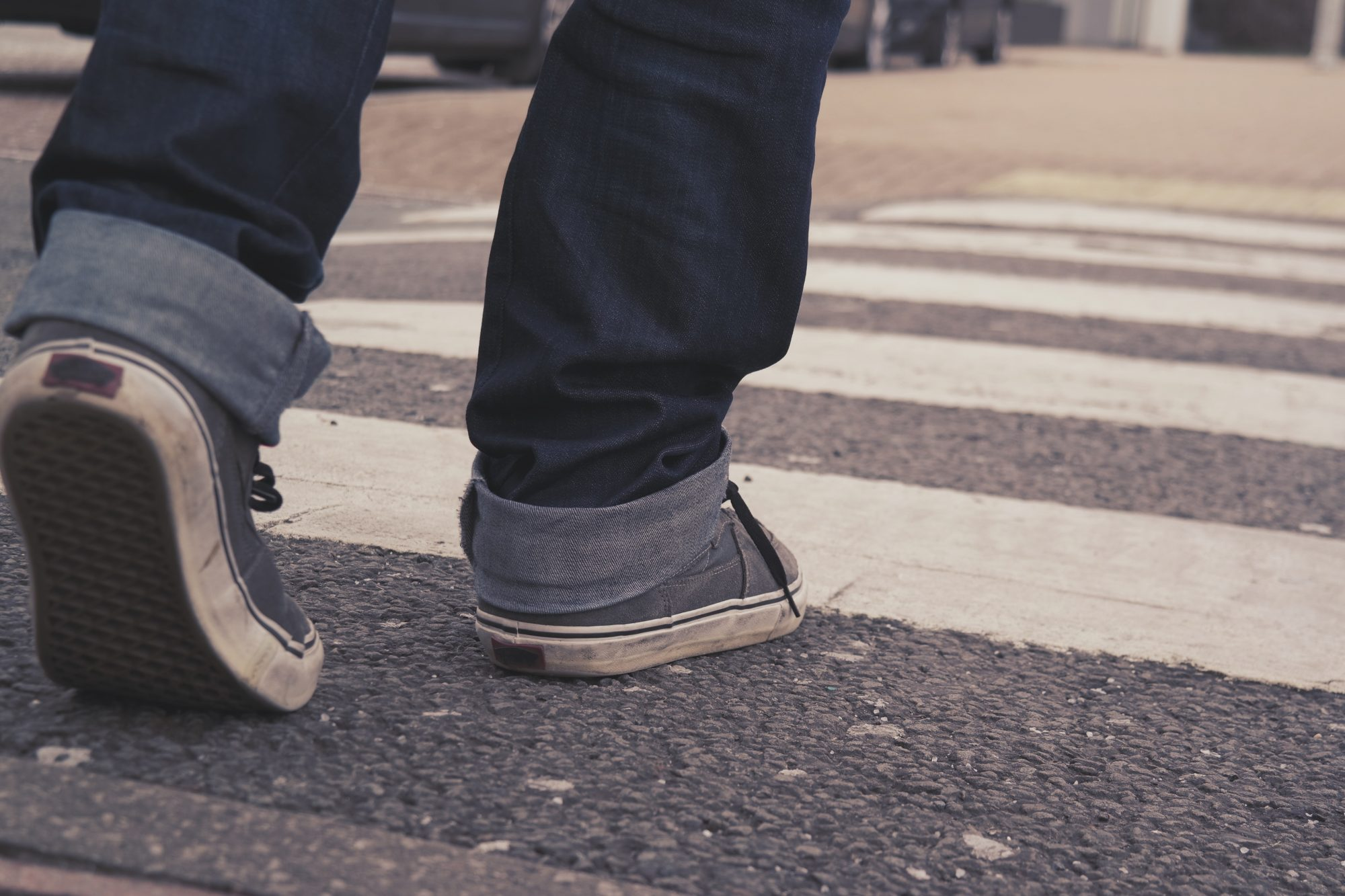 Man in Jeans and Sneakers Walking Across Crosswalk