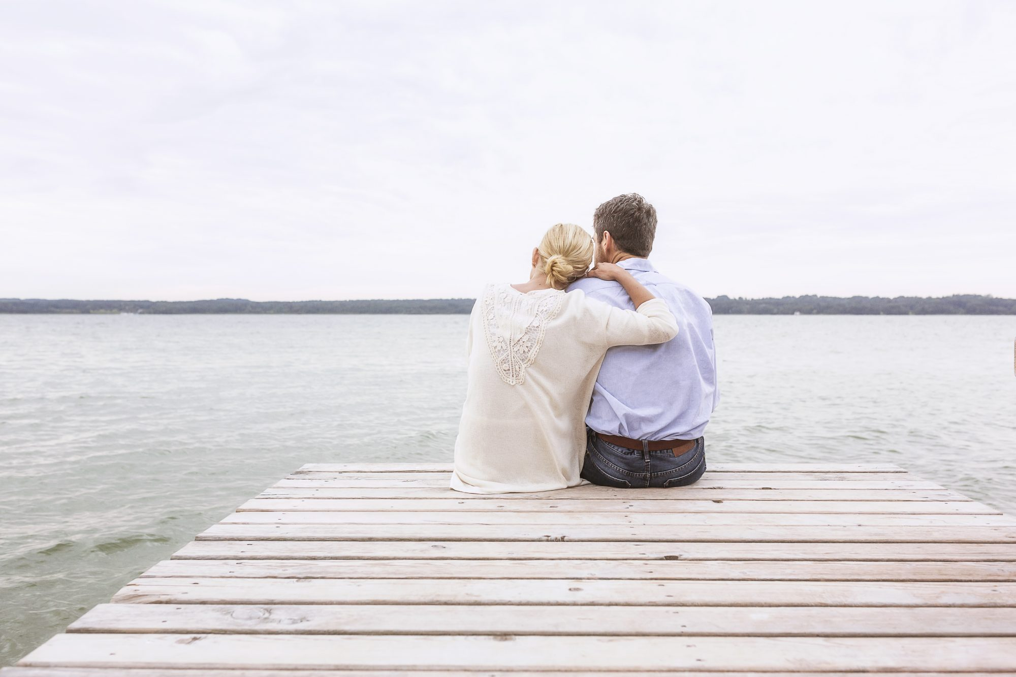 Couple Sitting on Pier Looking at Sea