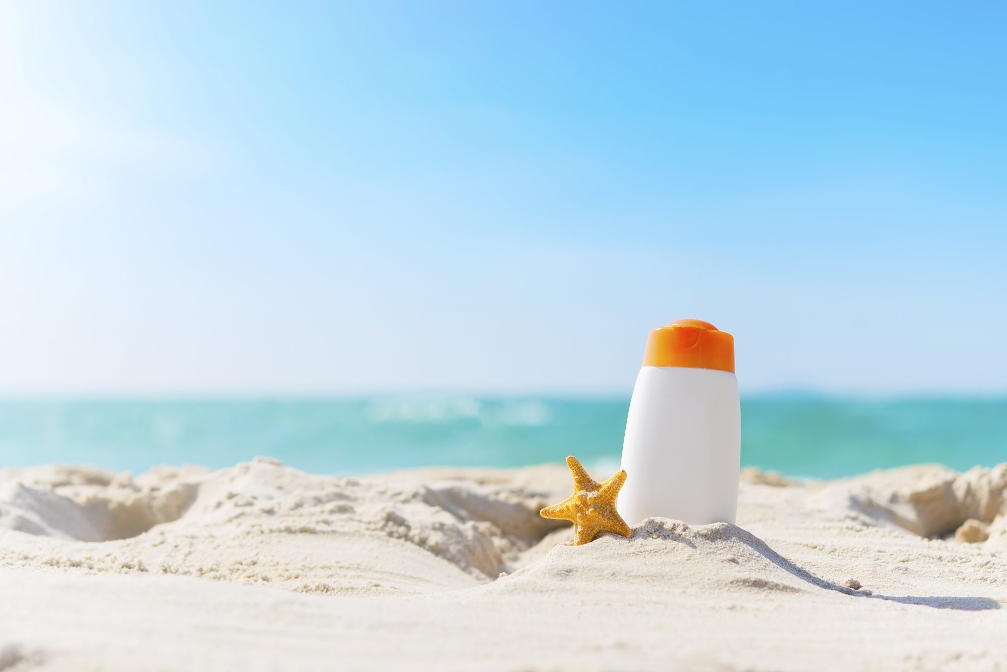 Sunscreen Tube and Starfish on Beach