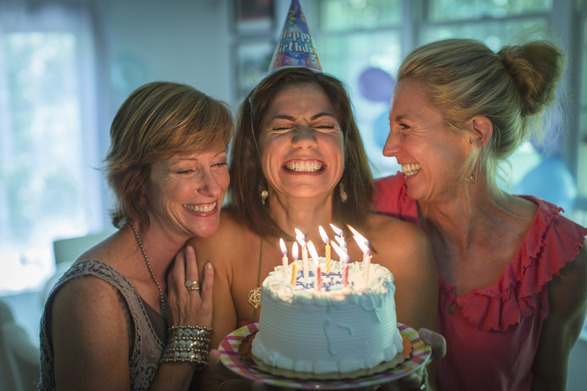Friends Laughing with Birthday Cake