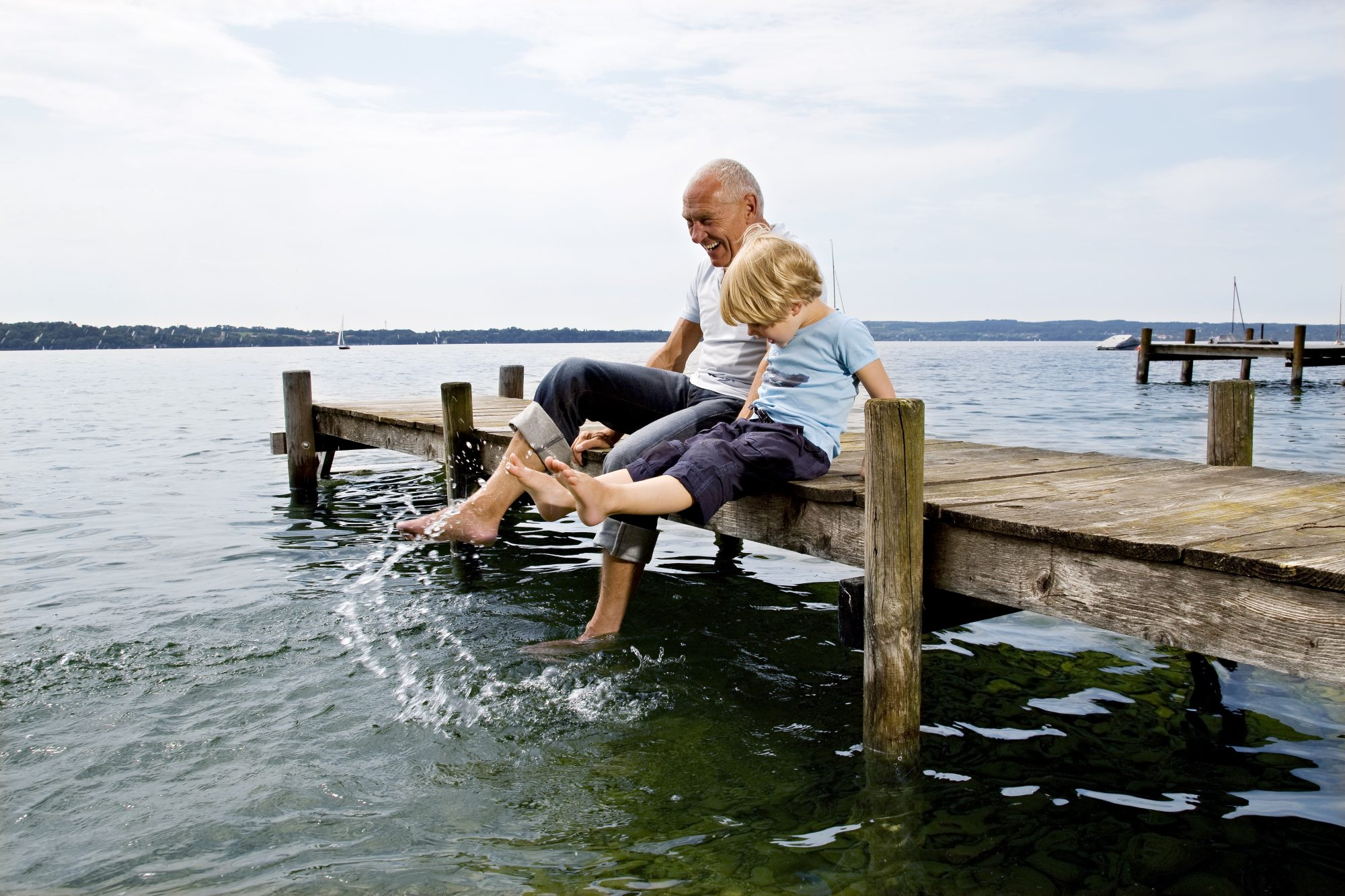 Grandfather and Grandson Splashing on Dock