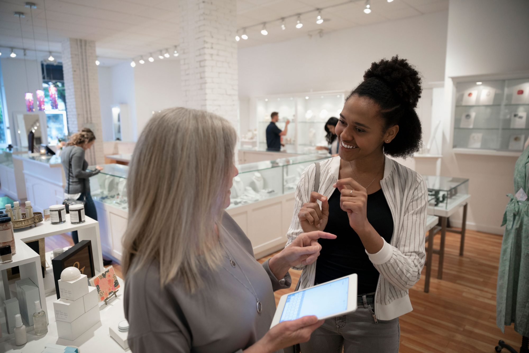 Woman checking with boutique owener