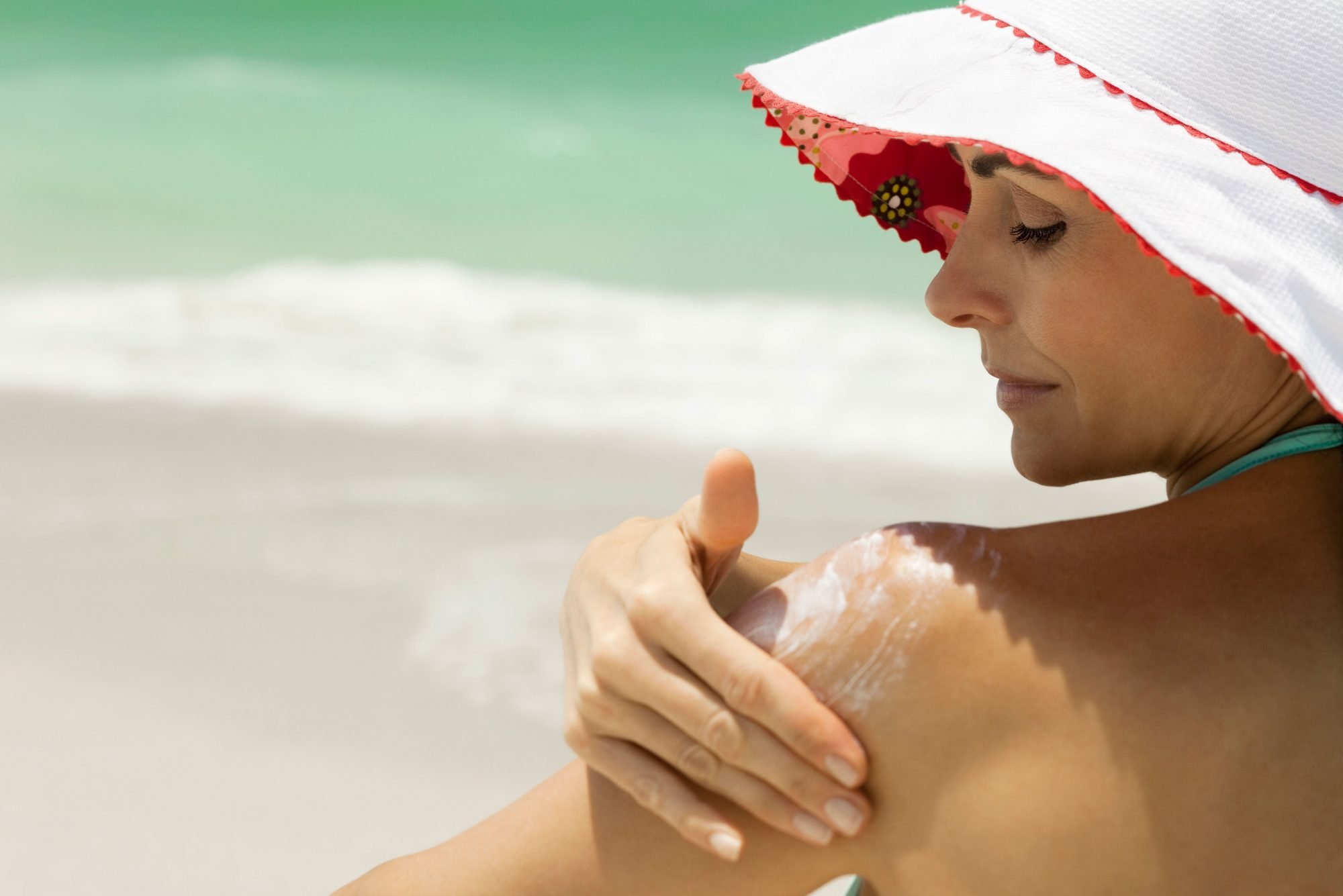 Woman Applying Sunscreen to Shoulders