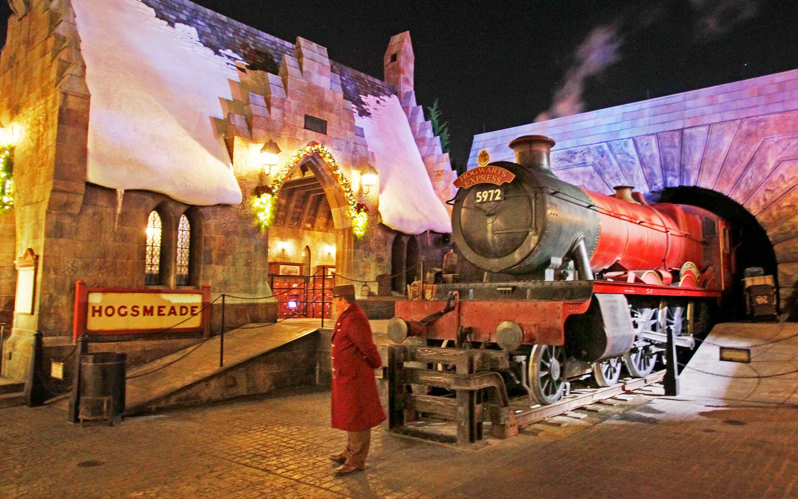 A steaming locomotive at Hogsmeade during a nighttime preview event of Christmas in the Wizarding World of Harry Potter