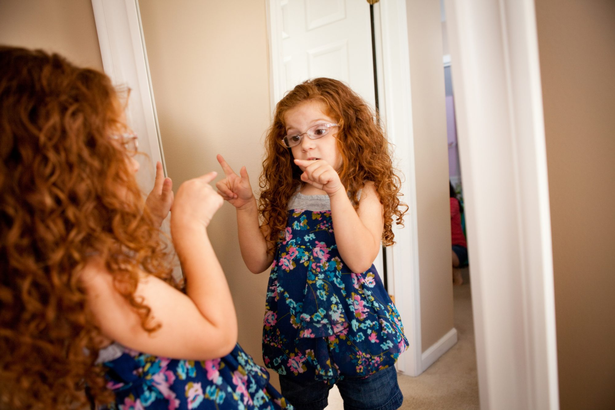Little Girl Talking to Herself in Mirror