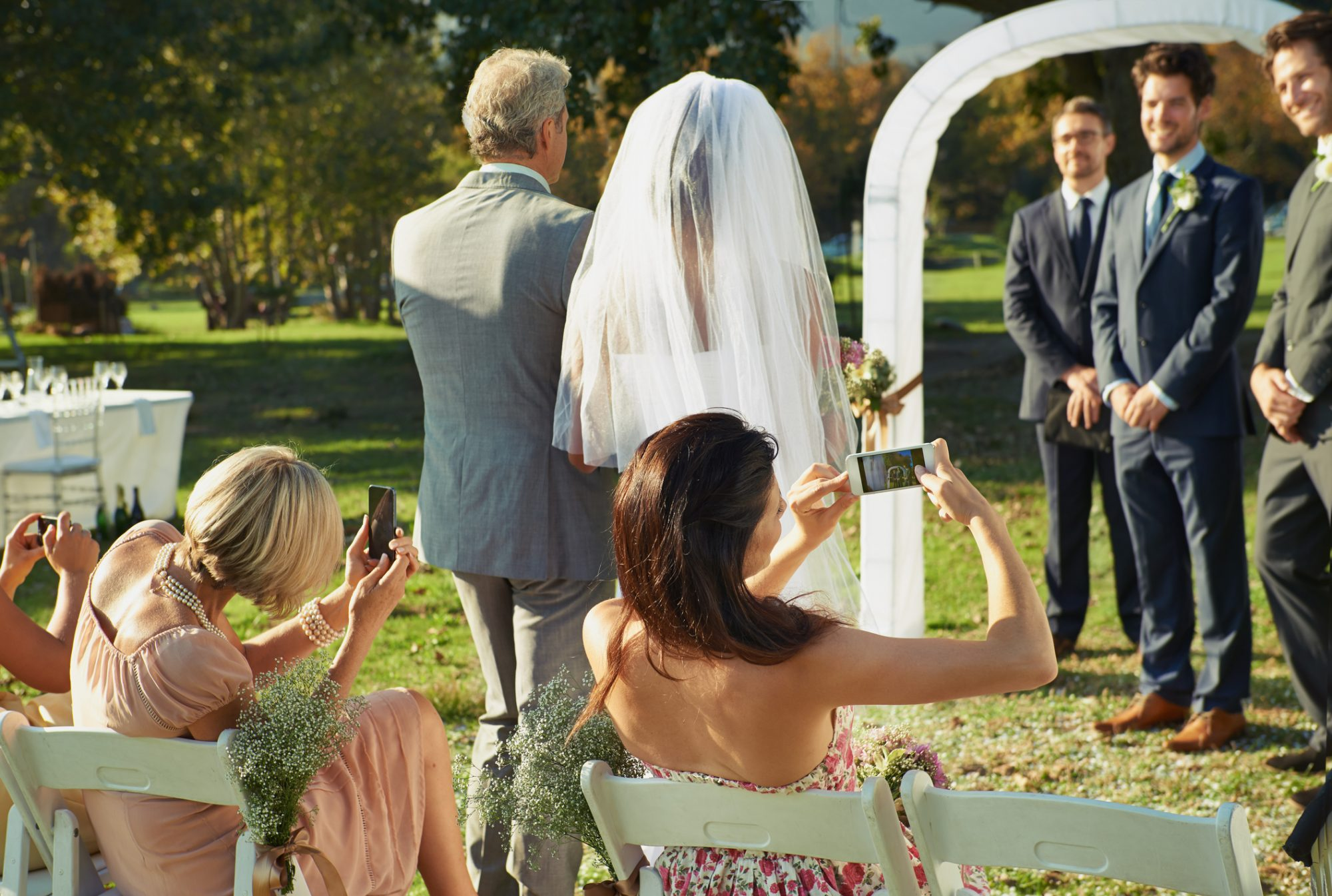 Wedding Guests Taking Pictures During Ceremony