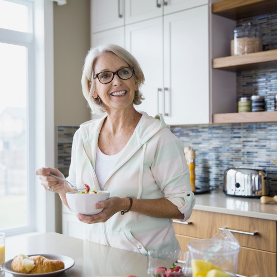 Here's Why You Shouldn't Stand and Eat, According to Research woman-eating-in-kitchen-0619-getty_sq
