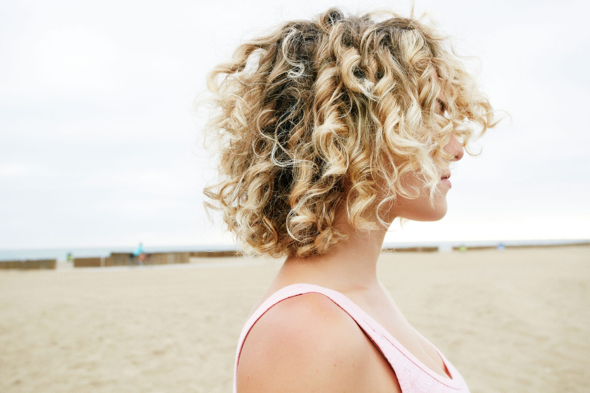 Woman with Blonde Curly Hair on the Beach