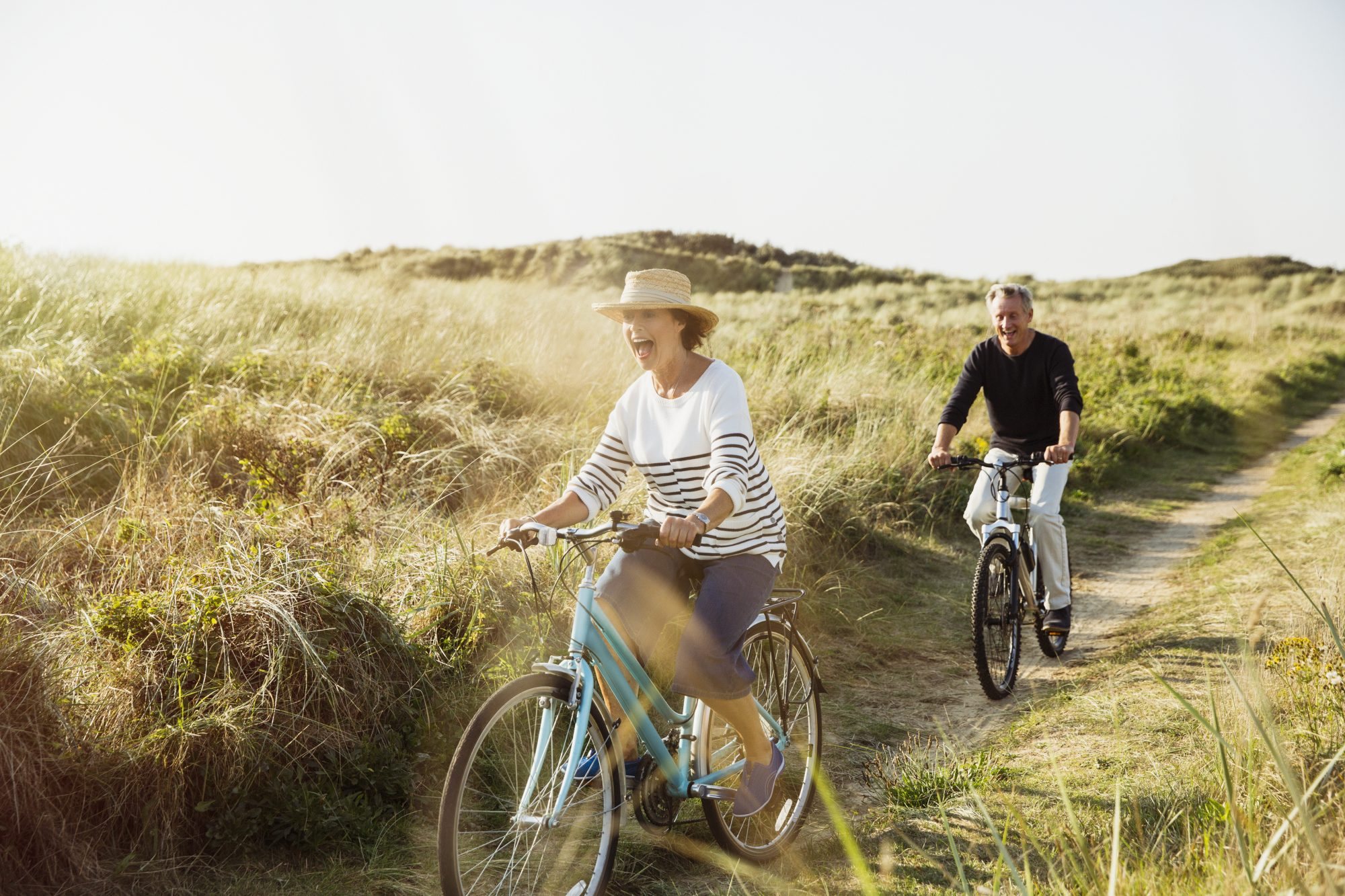 Retirement Couple Riding Bikes on Beach Path