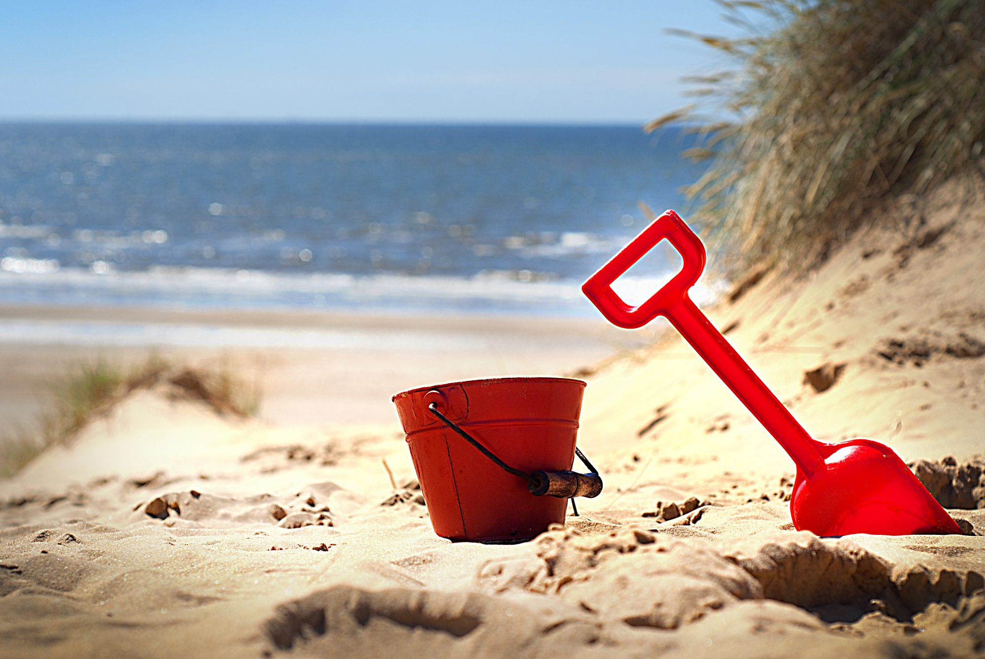 Red Bucket and Shovel in Sand on Beach