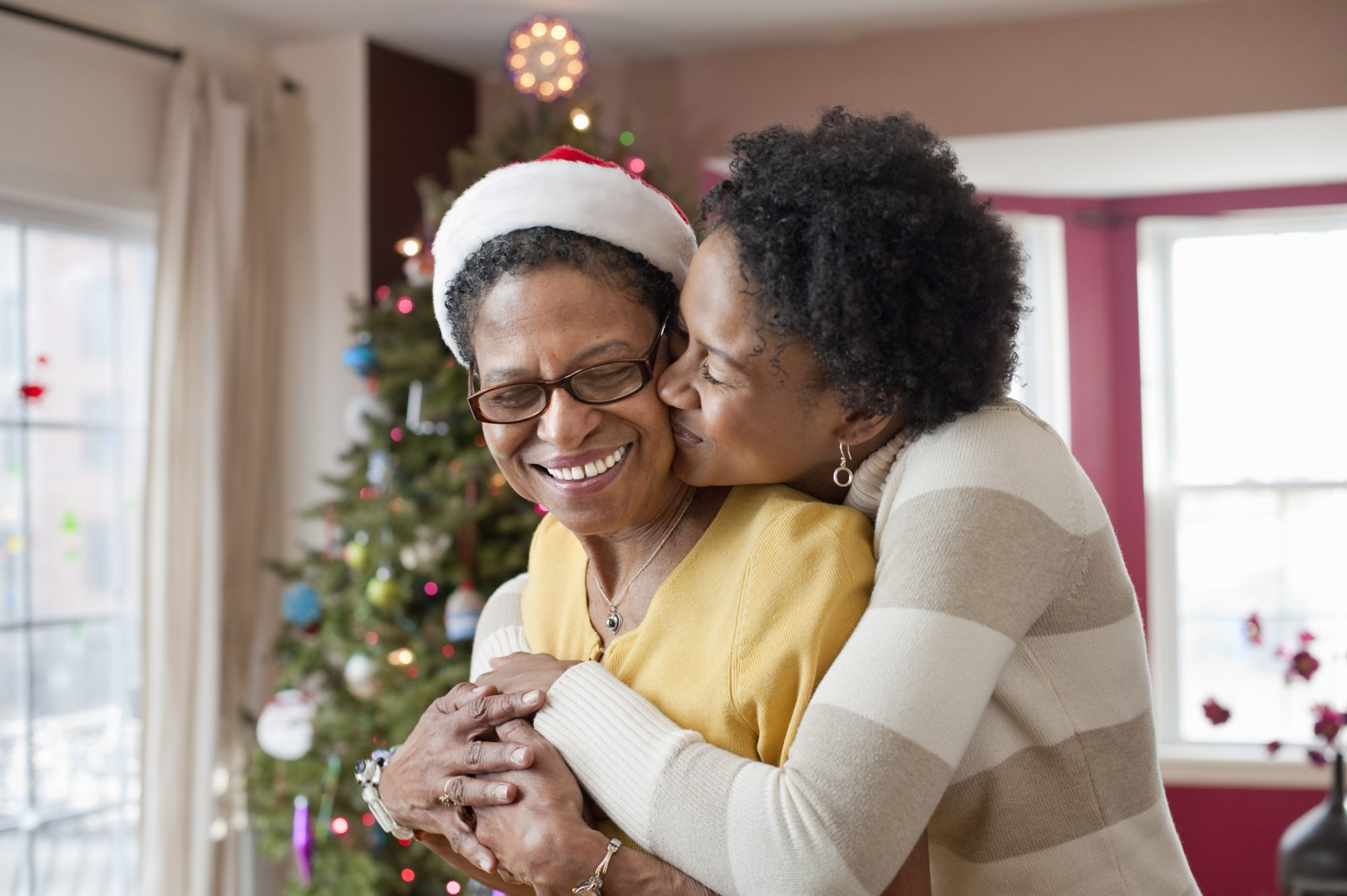 Mom and Daughter Hugging in front of Christmas Tree