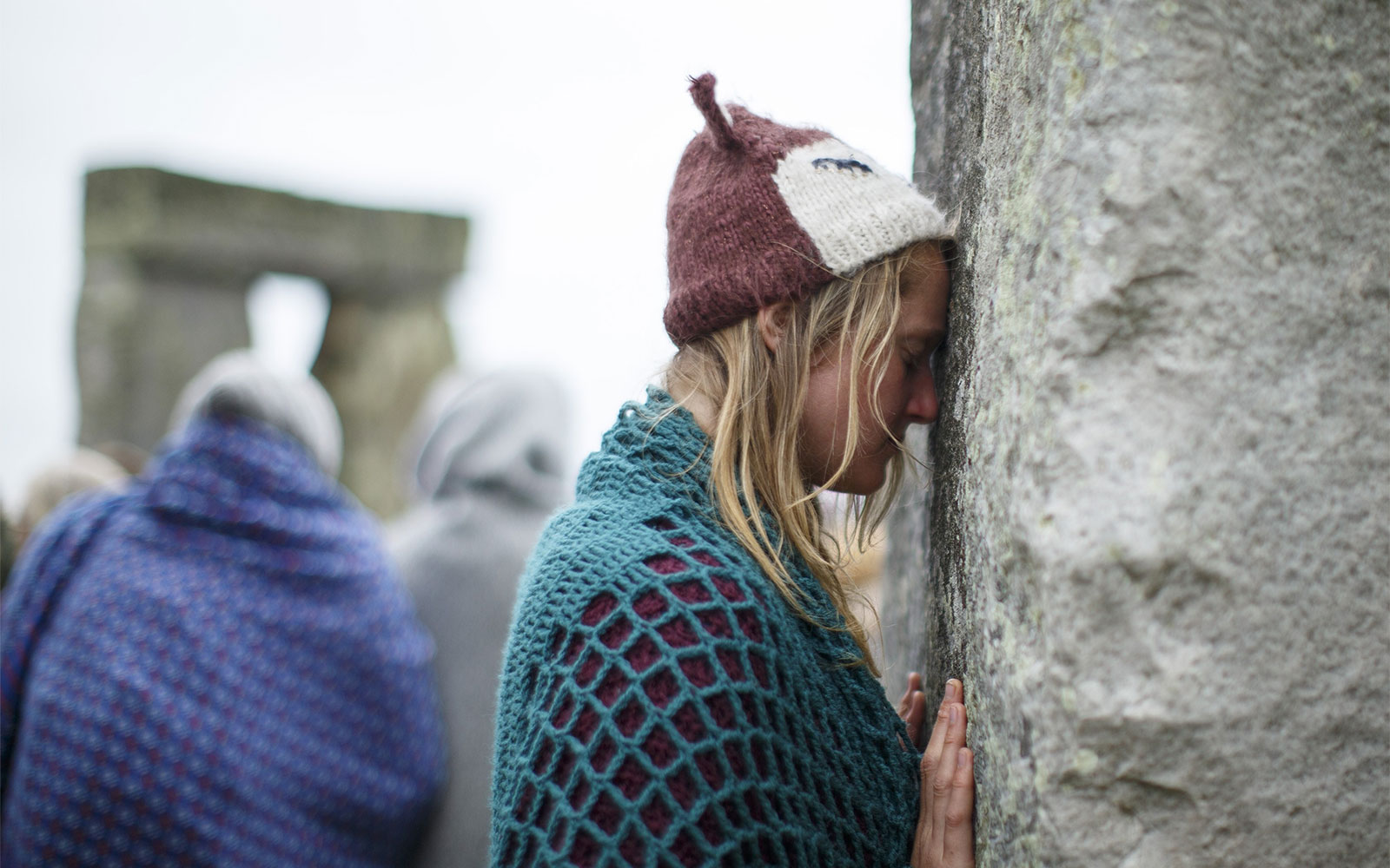SALISBURY, UNITED KINGDOM - JUNE 21: Revelers embrace the stones of Stonehenge during celebrations to mark the summer solstice at Stonehenge prehistoric monument on June 21, 2015 in Wiltshire, England. Thousands of revellers gather at the 5,000 year old stone circle in Wiltshire to see the sunrise on the Summer Solstice dawn. The solstice sunrise marks the longest day of the year in the Northern Hemisphere. (Photo by Tolga Akmen/Anadolu Agency/Getty Images)