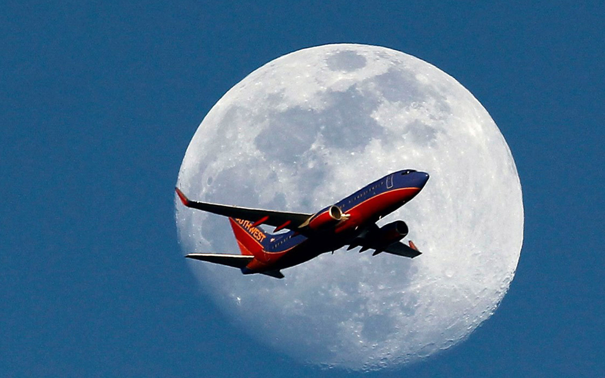 Photographers Capture Images of Airplanes Against Full Moon