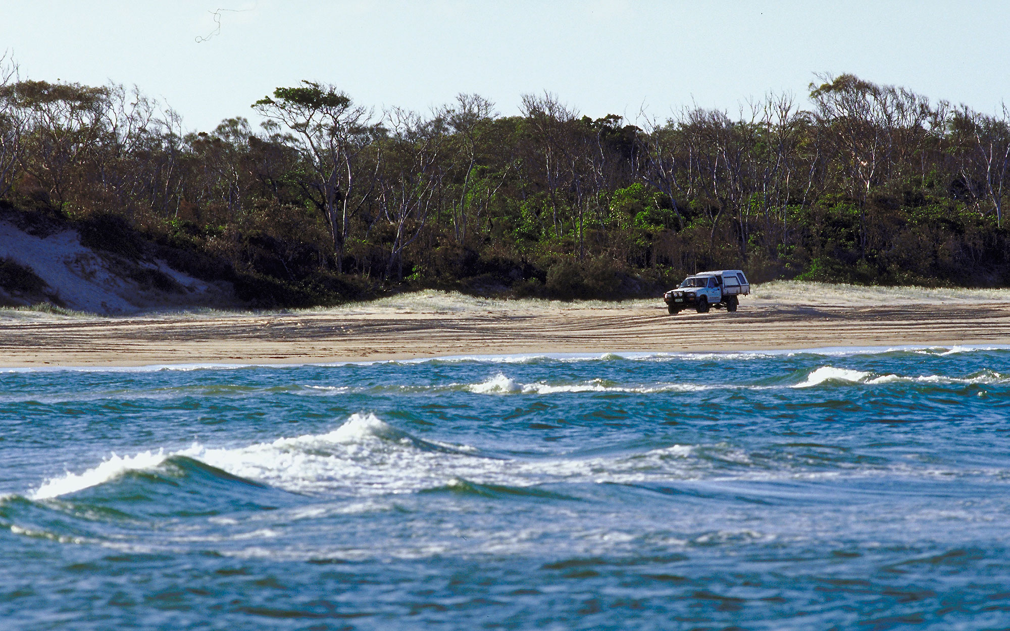 Truck driving at Teewah colored sands, Queensland, Australia