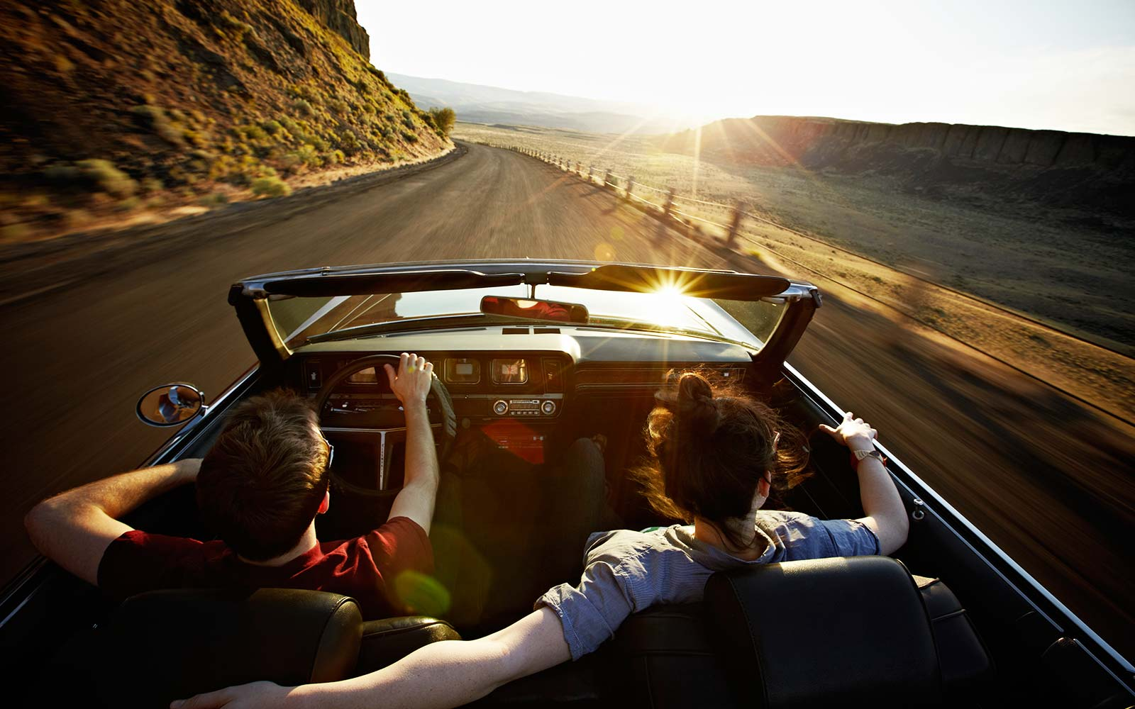 couple driving convertible sunset desert road