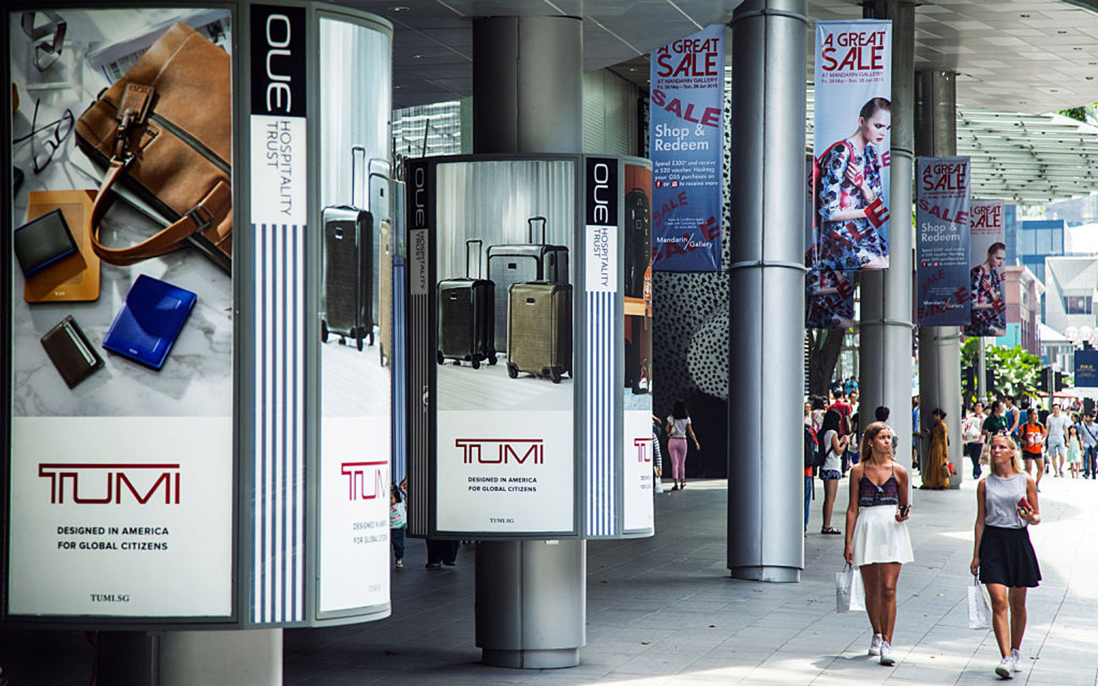 Shoppers walk past advertisements for Tumi Holdings Inc. on Orchard Road in Singapore, on Sunday, June 21, 2015. Consumer prices prices declined for a sixth straight month in April and employment contracted last quarter for the first time since 2009. Phot