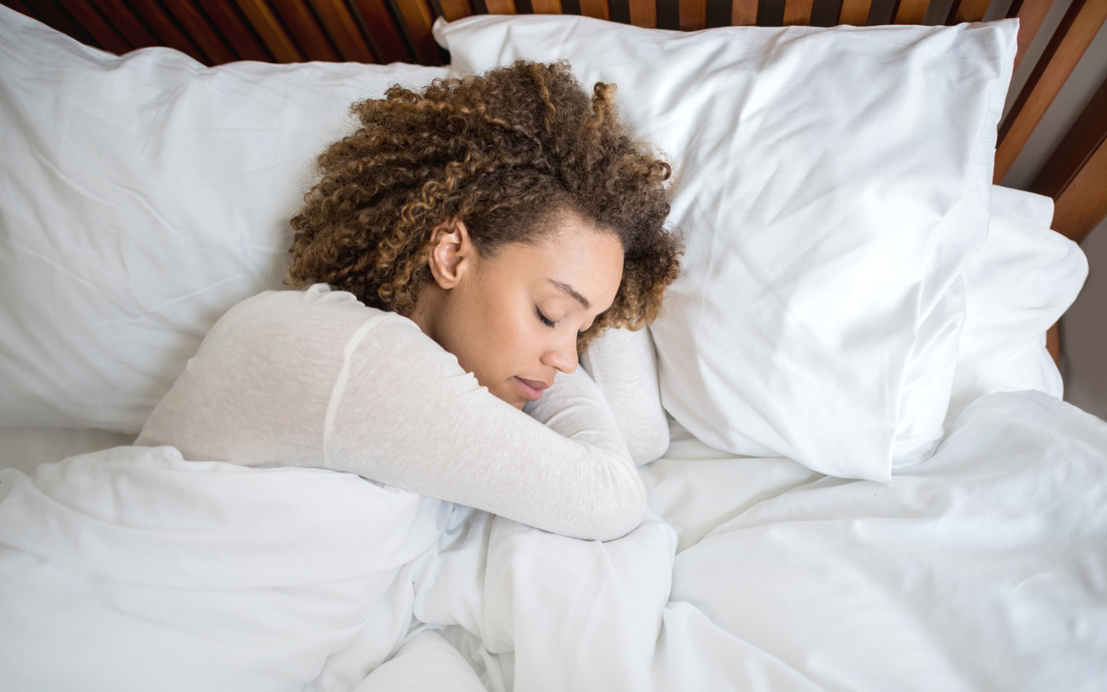 Tired African American woman sleeping in bed at home