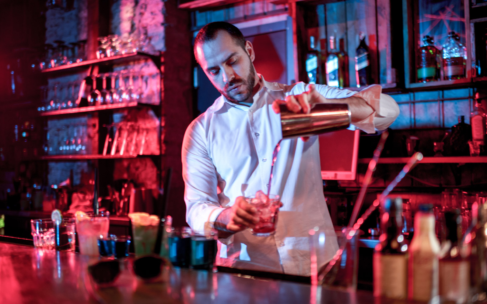 Bartender in white shirt pouring a cocktail into glass.
