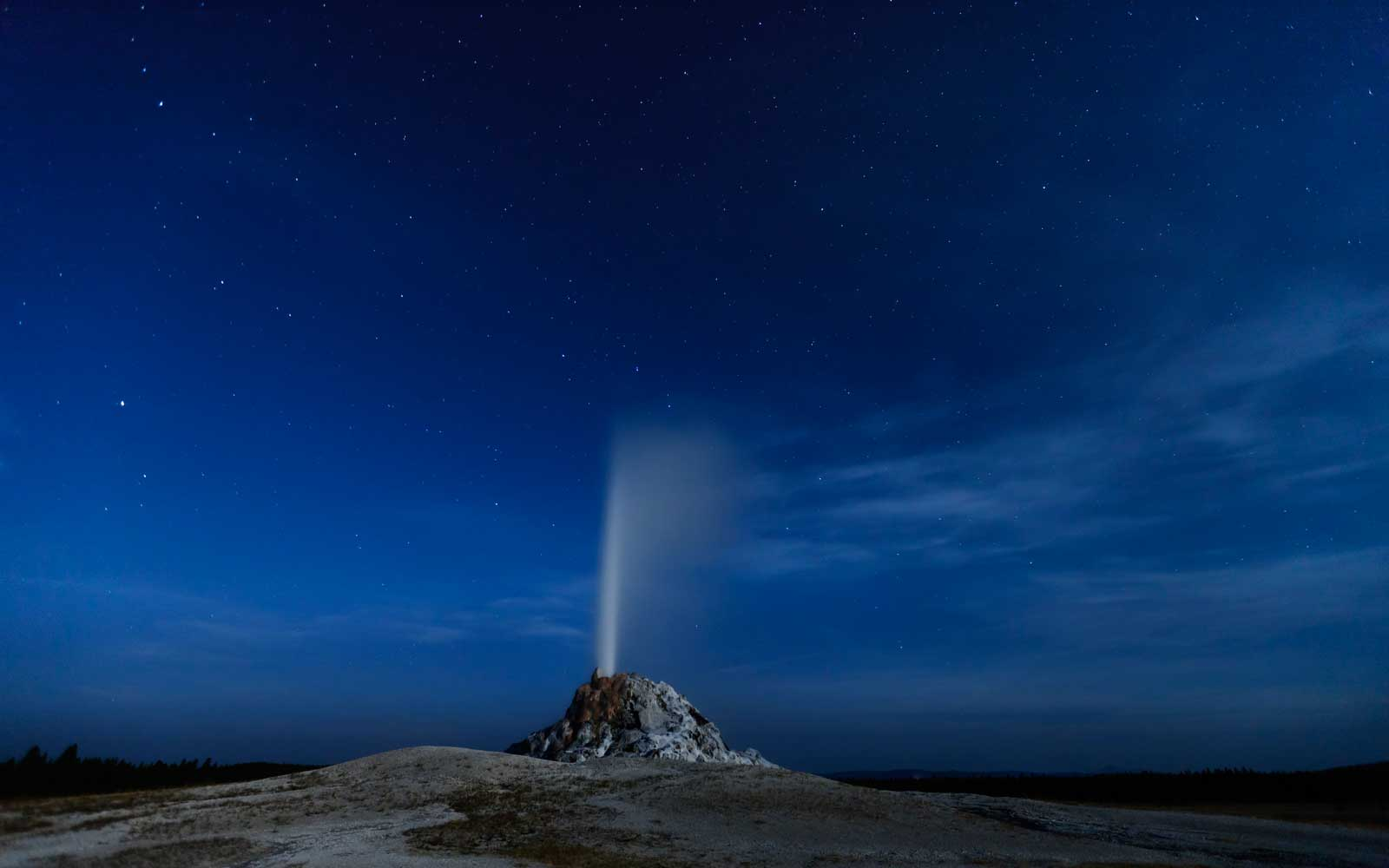 The White Cone Geyser, lit only by the light of a full moon, erupts under a star-filled sky in Yellowstone National Park, Wyoming, USA.