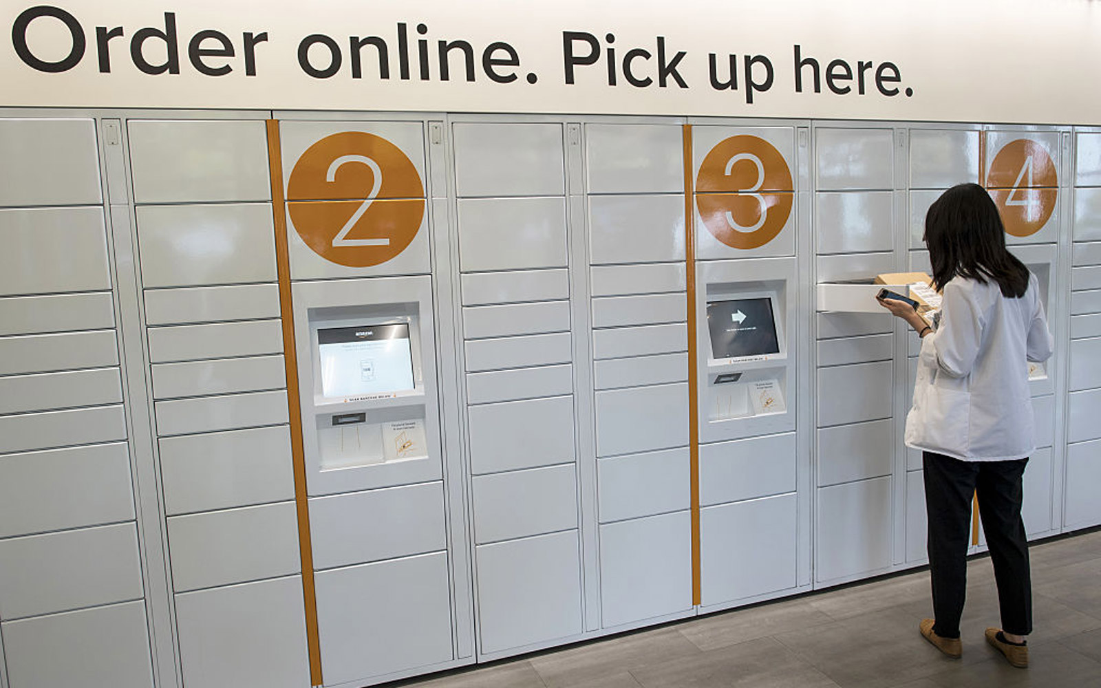 A student retrieves a package at the Amazon.com Inc. kiosk on the University of California, Berkeley campus in Berkeley, California, U.S., on Wednesday, Oct. 12, 2016. By the end of the year, Amazon will have staffed pickup kiosks serving more than 500,00