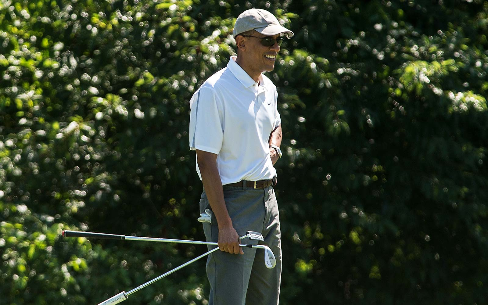 US President Barack Obama smiles as he watches his golfing partners putt on the first green while playing at the Farm Neck Golf Club at Martha's Vineyard, Massachusetts on the first day of the president's yearly summer vacation