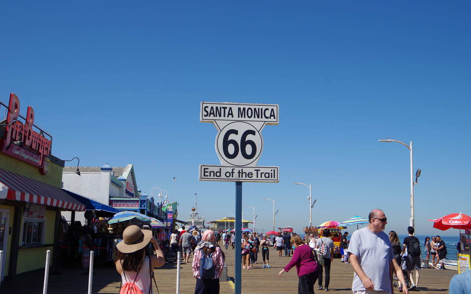 Santa Monica, USA – April 30, 2017: Route 66 Santa Monica End of Trail sign on Santa Monica Pier.  Route 66 opened in 1926 connects from Chicago to Santa Monica and has a total length of 3755 km. A lot of people visit here.