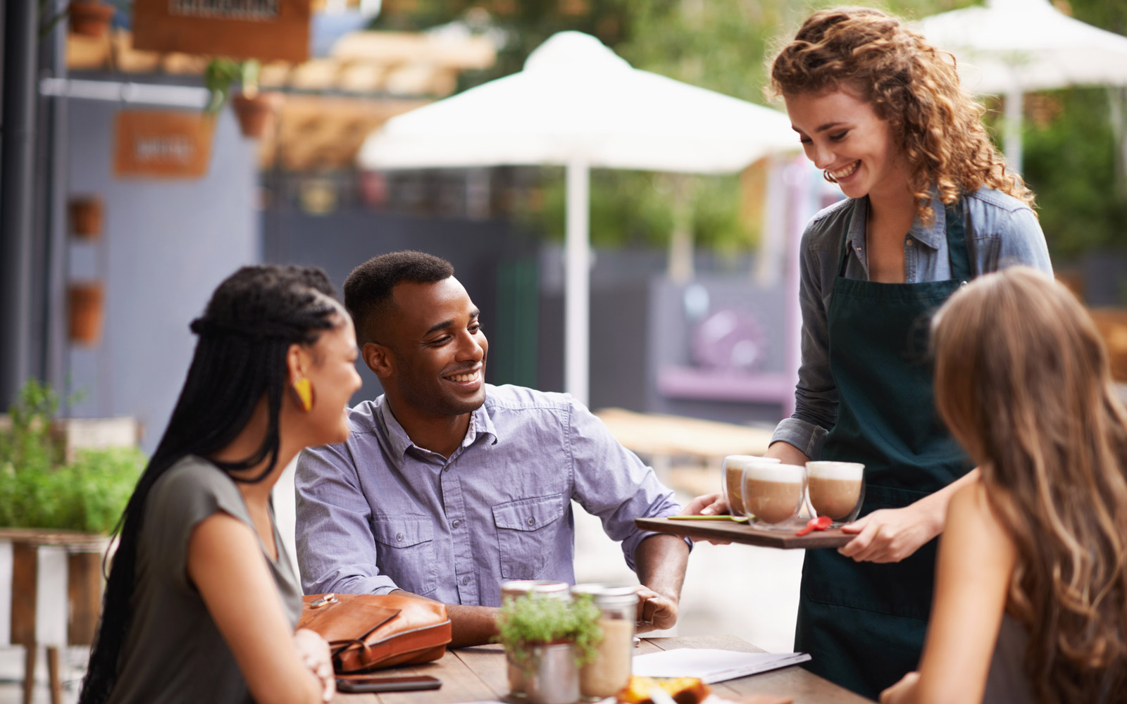 Cropped shot of a waitress serving her customers at a coffee shop