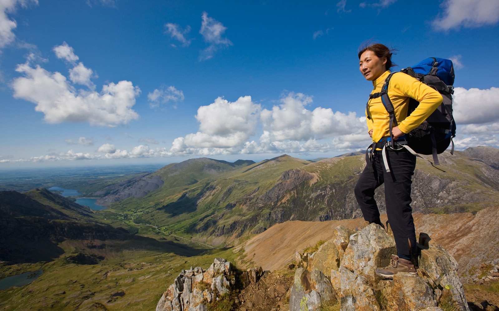woman with rucksack on top of a mountain close to Mt.Snowdon in Wales