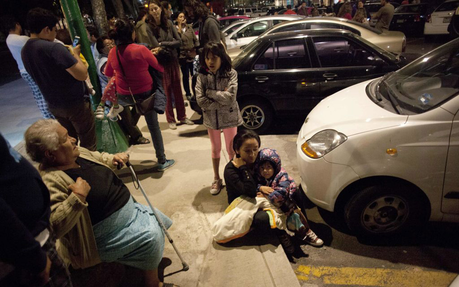 People sitting outside after an earthquake hit southern Mexico