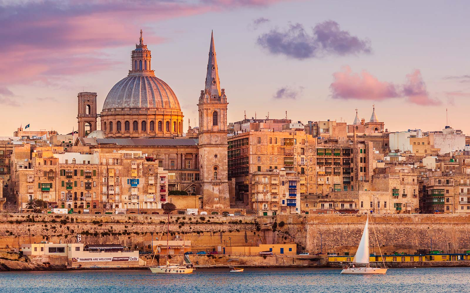 Valletta skyline at sunset with the Carmelite Church dome and St. Pauls Anglican Cathedral, Valletta, Malta, Mediterranean, Europe Viking Cruises