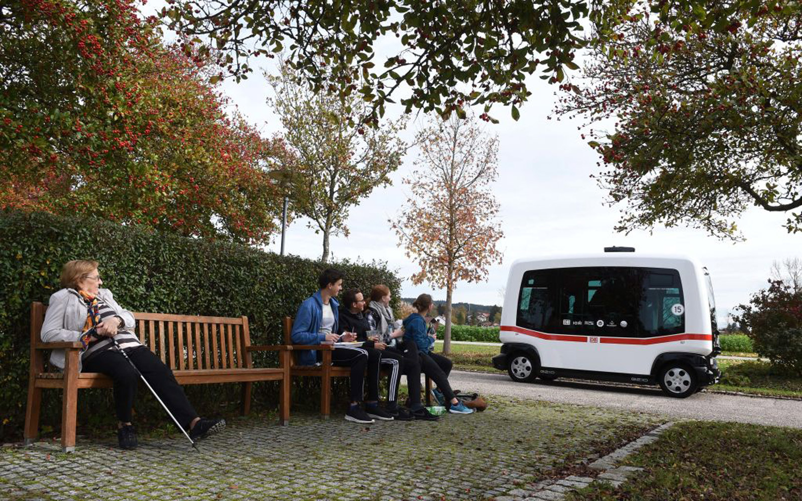 People watch the first German autonomous public transport bus which drives during a presentation beside a park in Bad Birnbach