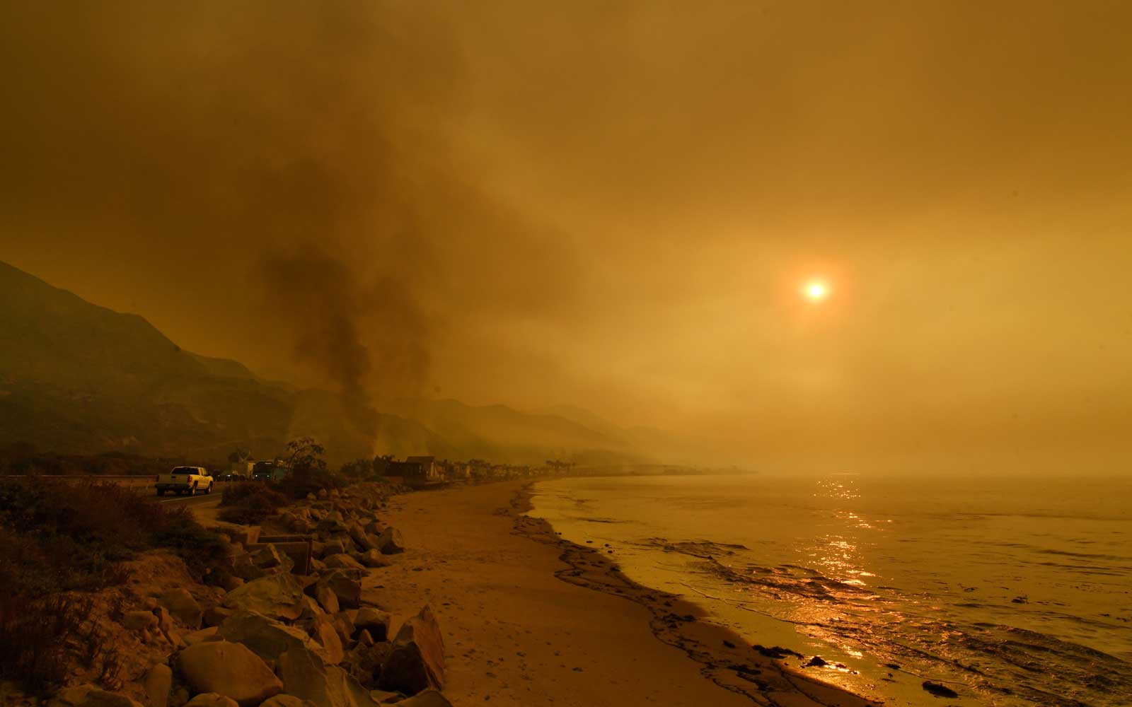 Heavy smoke covers the seaside enclave of Mondos Beach beside the 101 highway as flames reach the coast during the Thomas wildfire near Ventura, California