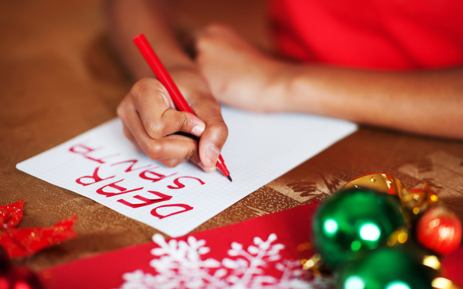 Unrecognizable child writing a letter to Santa Claus and making a present wish list.
