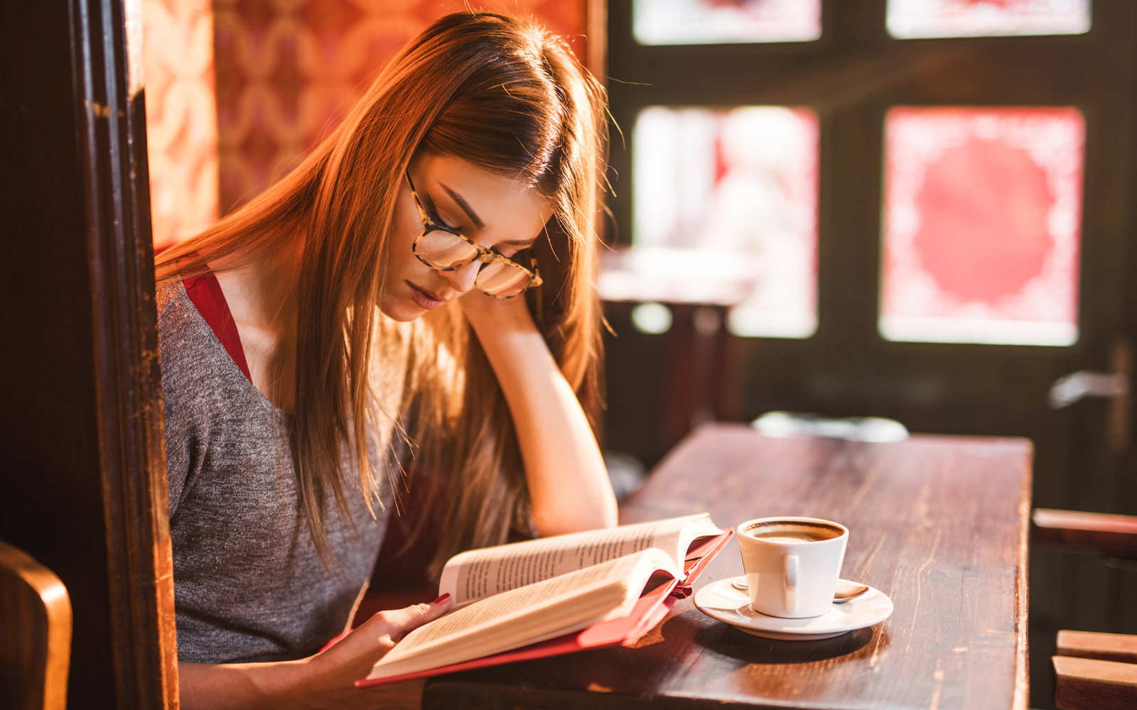 Young beautiful woman reading a book in a cafe