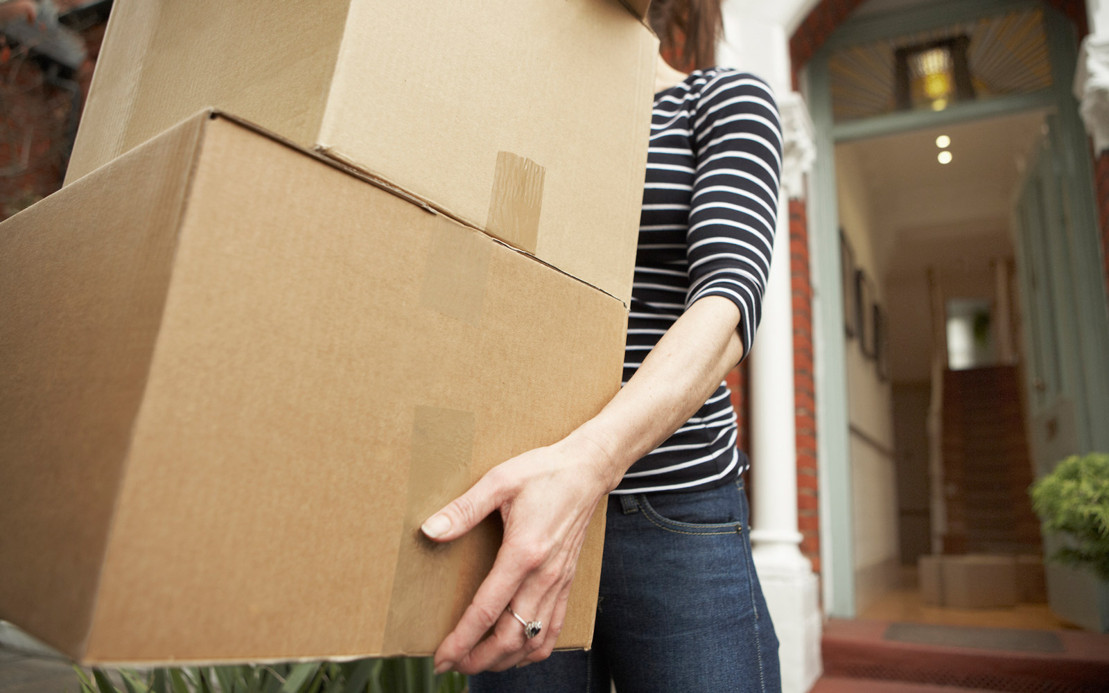 Woman carrying brown boxes from house