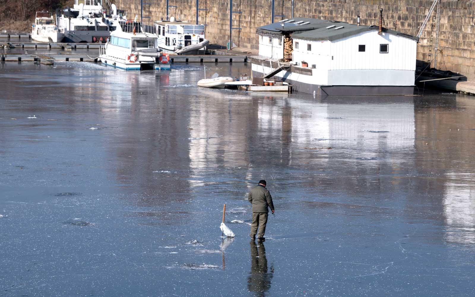 An ice fisherman stands on the ice of a frozen harbor basin of the Elbe in Dresden, Germany, on February 28, 2018