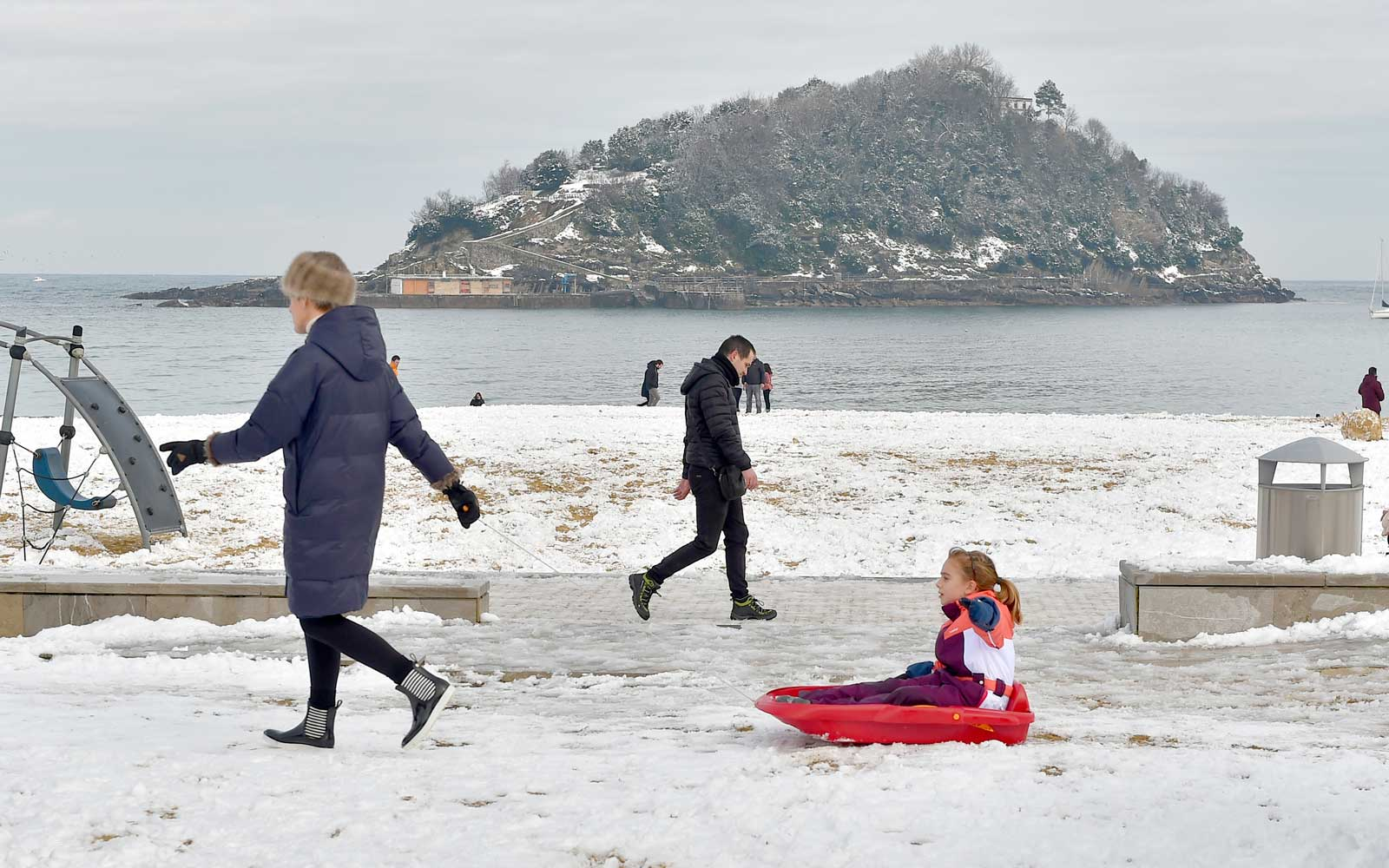 A man pulls his child along in a sledge at the Ondarreta beach in San Sebastian, northern Spain, after a heavy snowfall on February 28, 2018.
