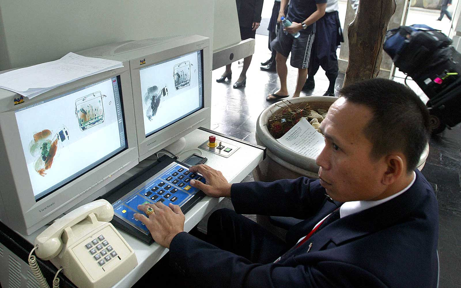 Thai security officer checks bags with an x-ray machine at the Grand Hyatt Erawan