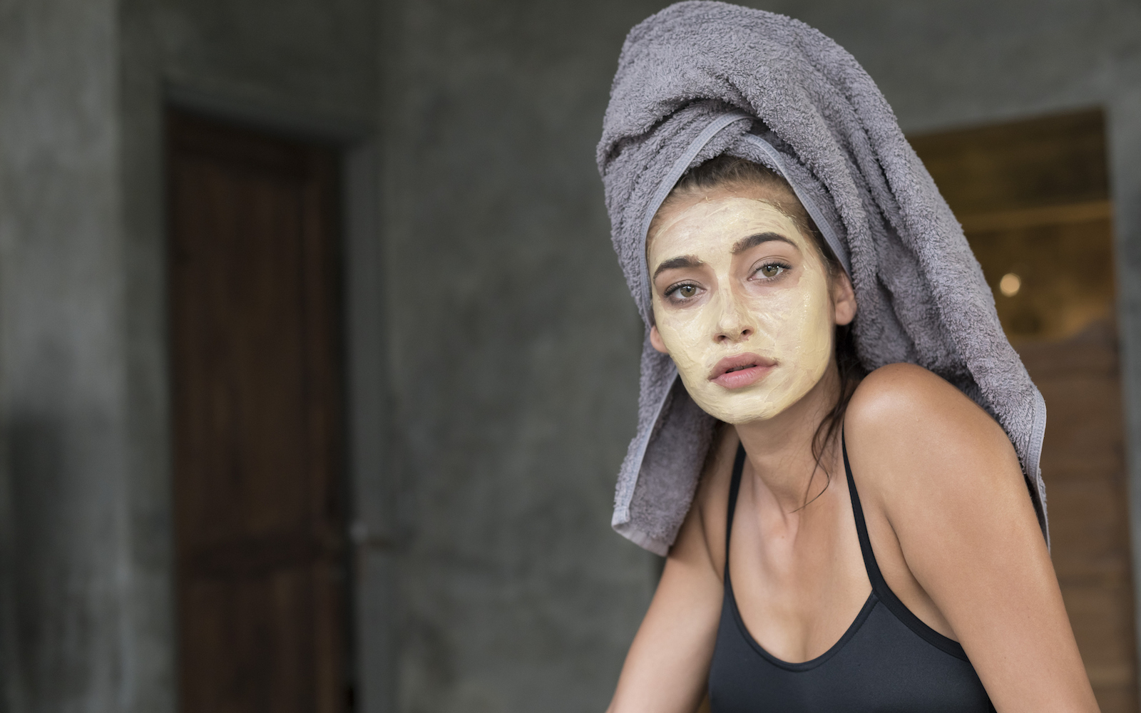 a woman doing a face mask after showering
