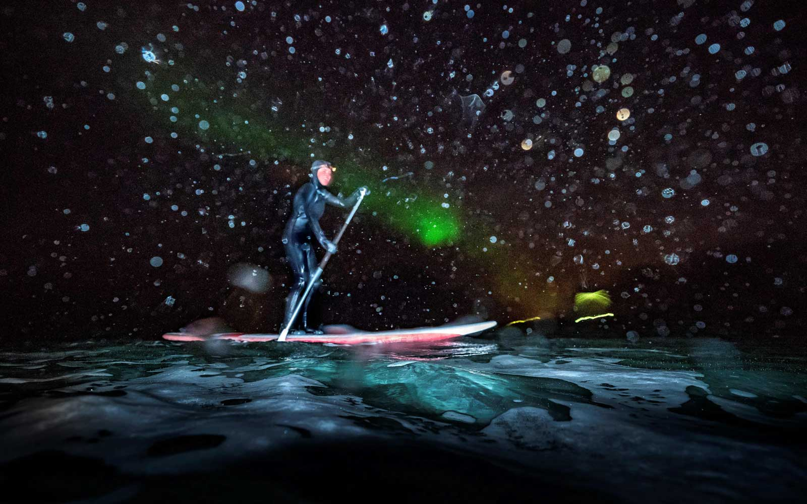 Myrtille Heissat from France rides a SUP (Stand Upp Paddle) under Northern Lights, on March 8, 2018 in Unstad northern Norway, Lofoten islands, within the Arctic Circle.