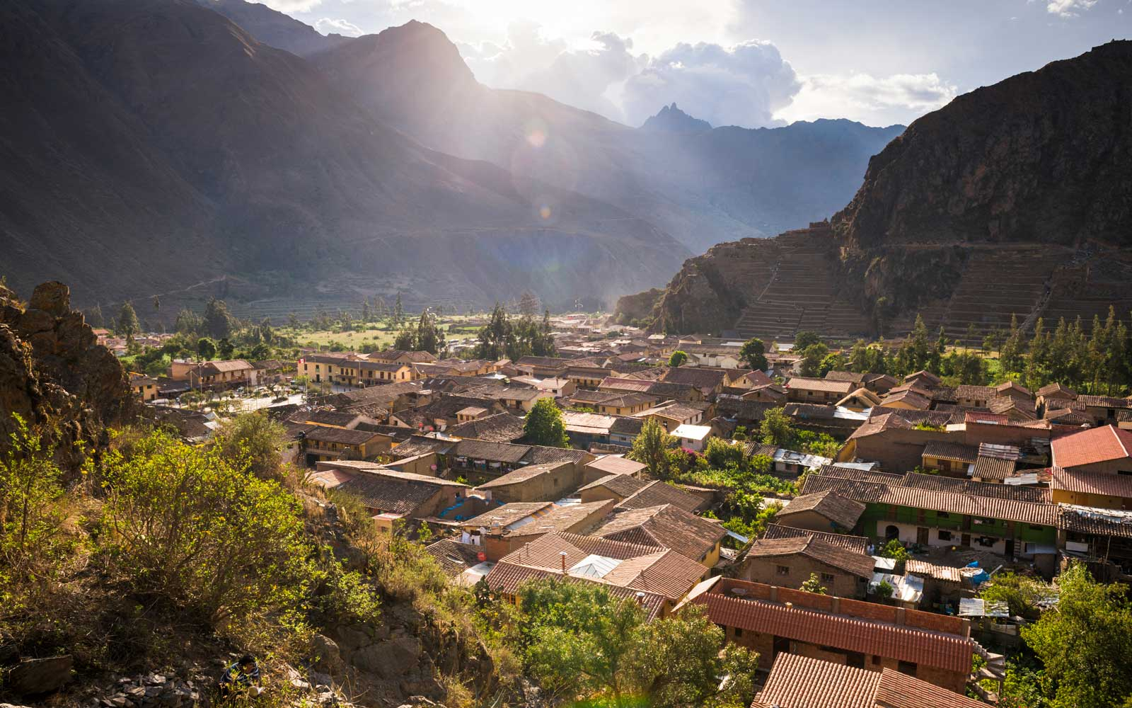 Ollantaytambo Inca Ruins at sunset seen behind Ollantaytambo Town, Peru