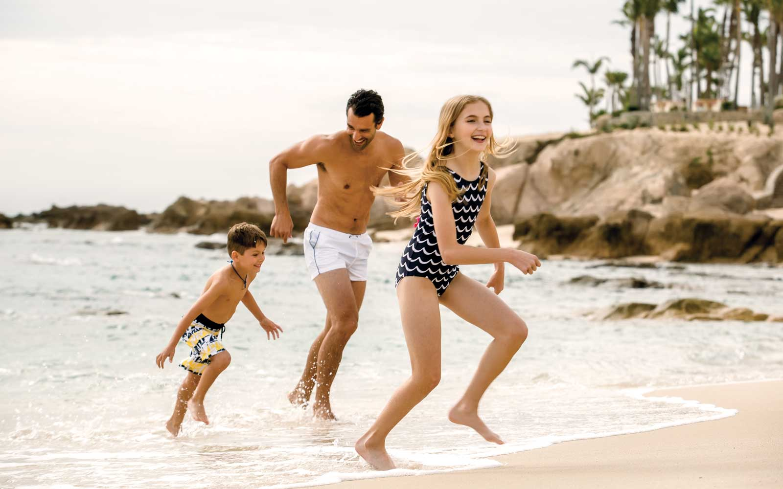 Family running on the beach at One & Only Resorts