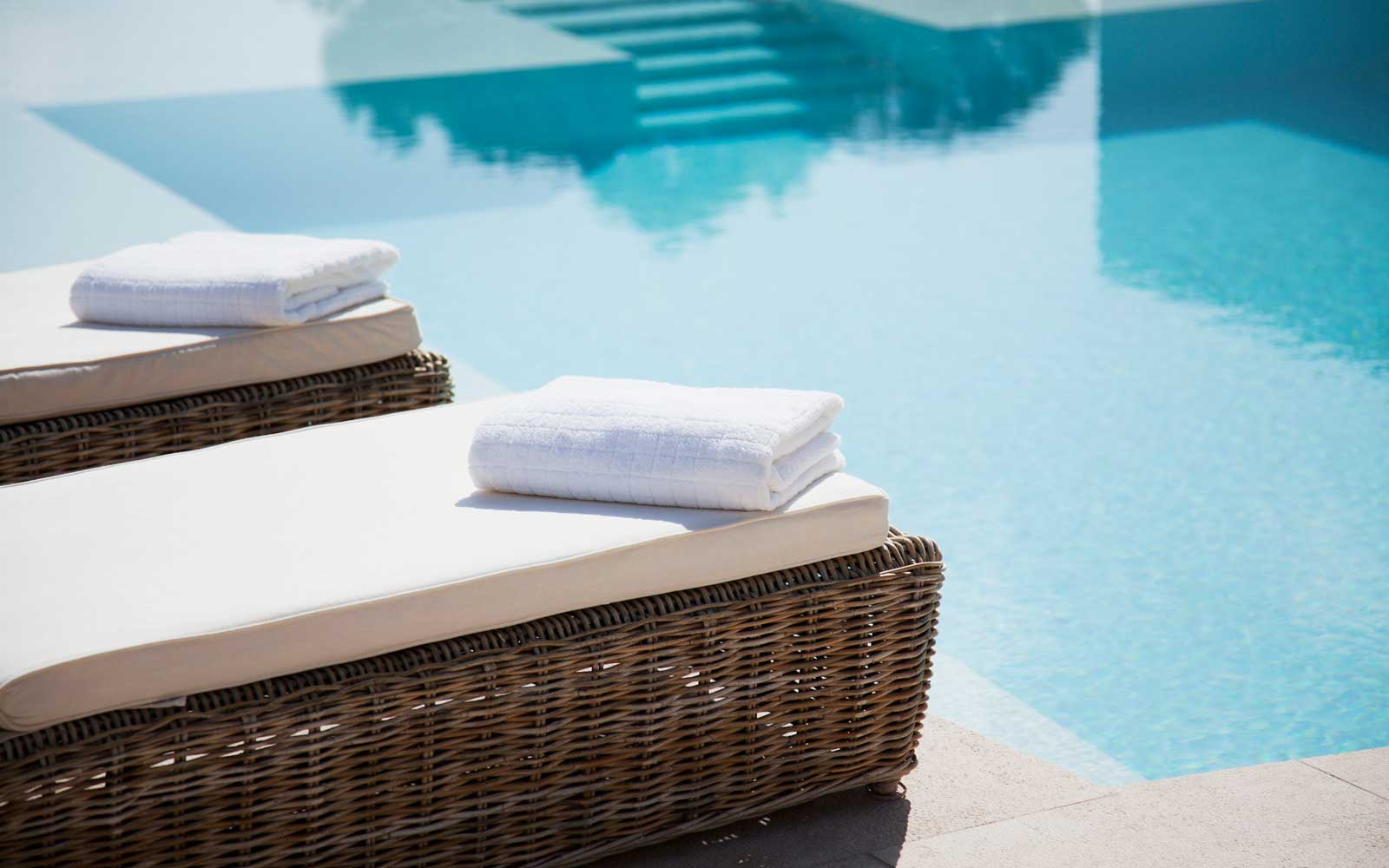 Folded towels on lounge chairs beside pool