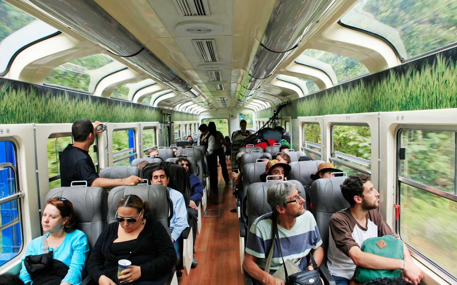Tourists en route to Machu Picchu admire the scenery through panoramic windows of the Vistadome train