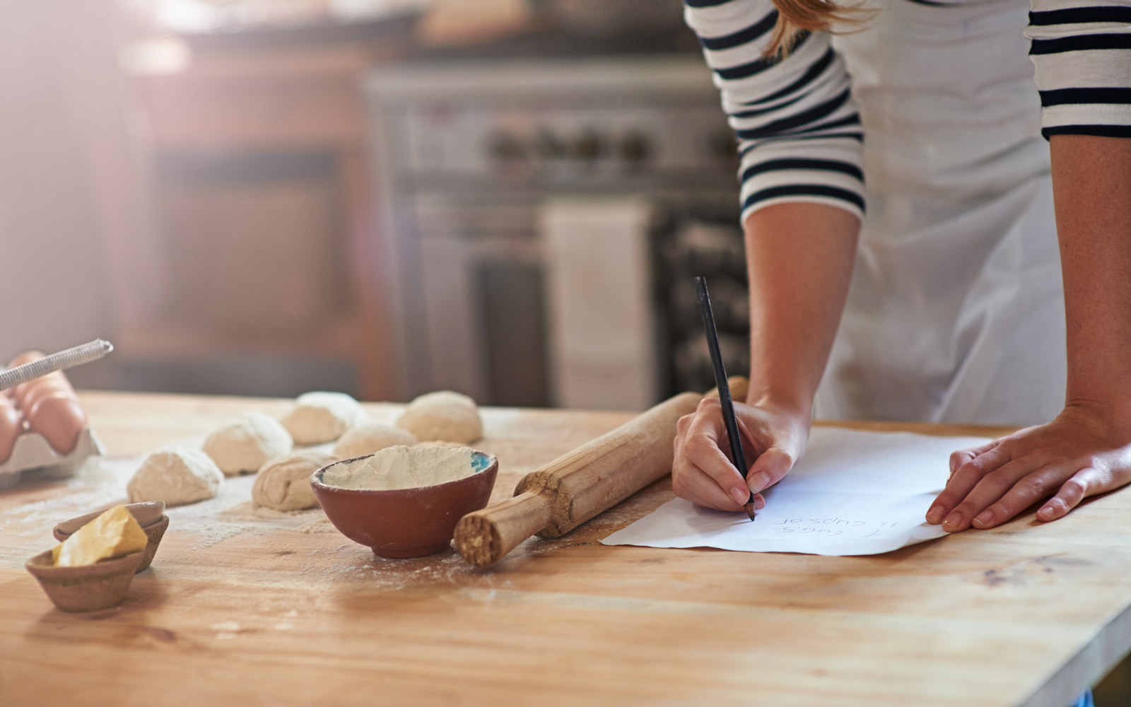 Cropped shot of a woman writing a recipe for the dough that she's preparing