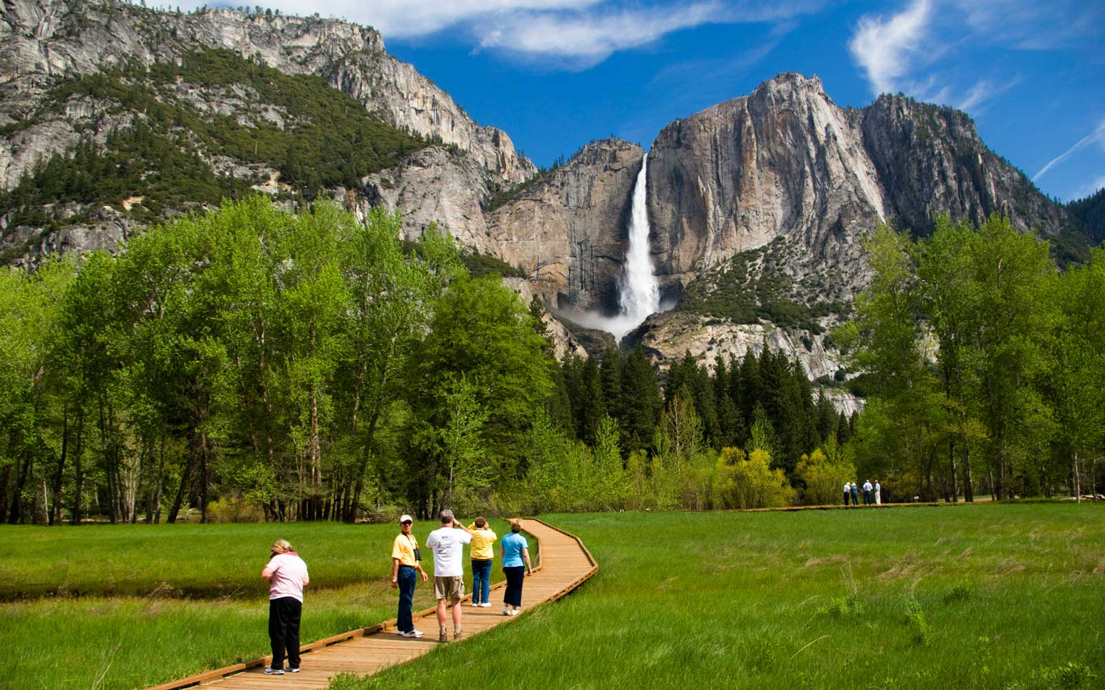 People looking at Yosemite Falls from  wooden walkway.