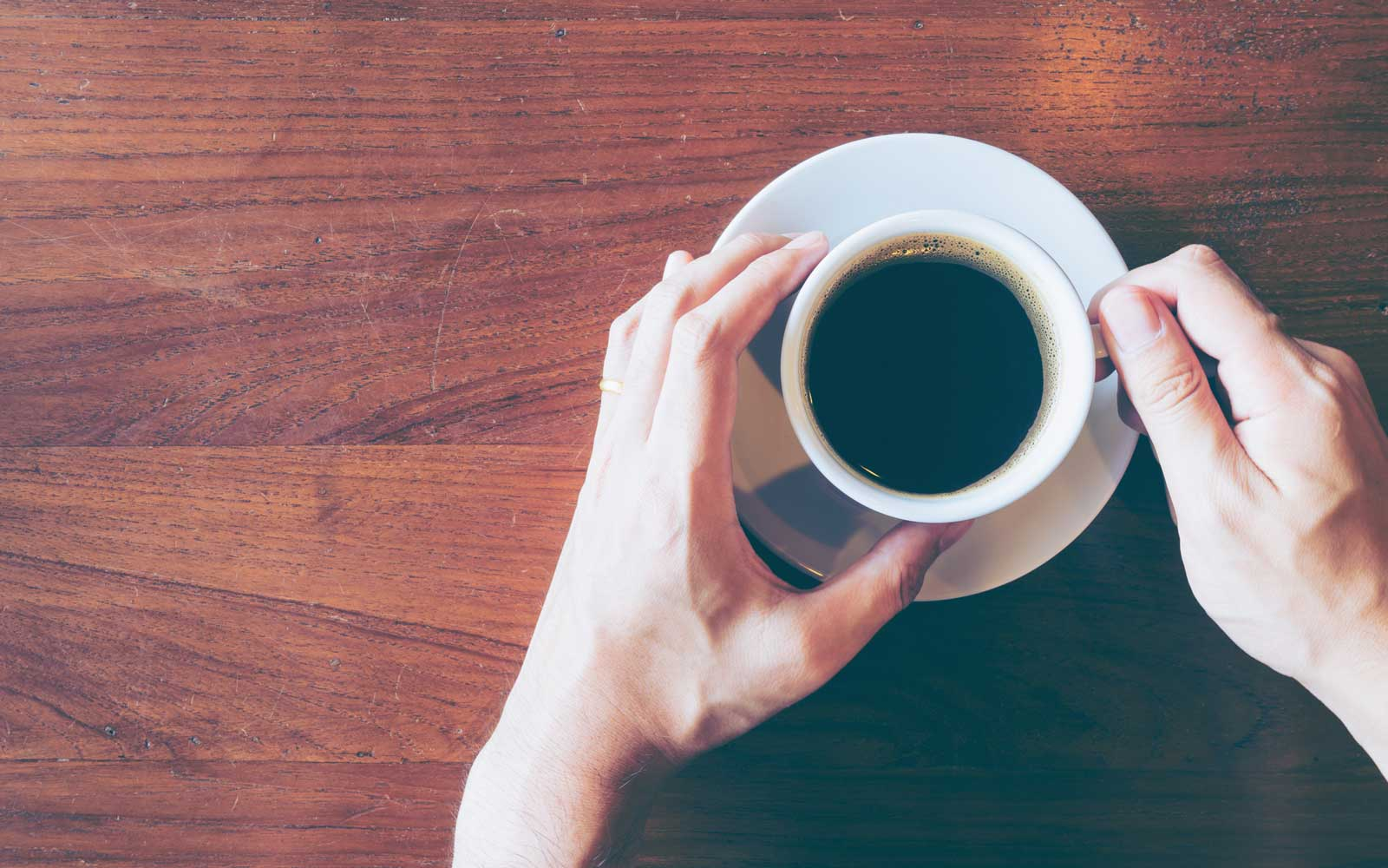 Cropped Hands Holding Coffee Cup On Table